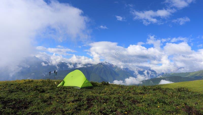 Tenda del _ s della viandante sull'alta montagna, con le montagne della neve nei precedenti immagine stock