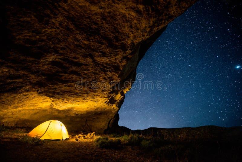 Tenda di campeggio d'ardore nella grotta di notte sotto un cielo stellato fotografie stock