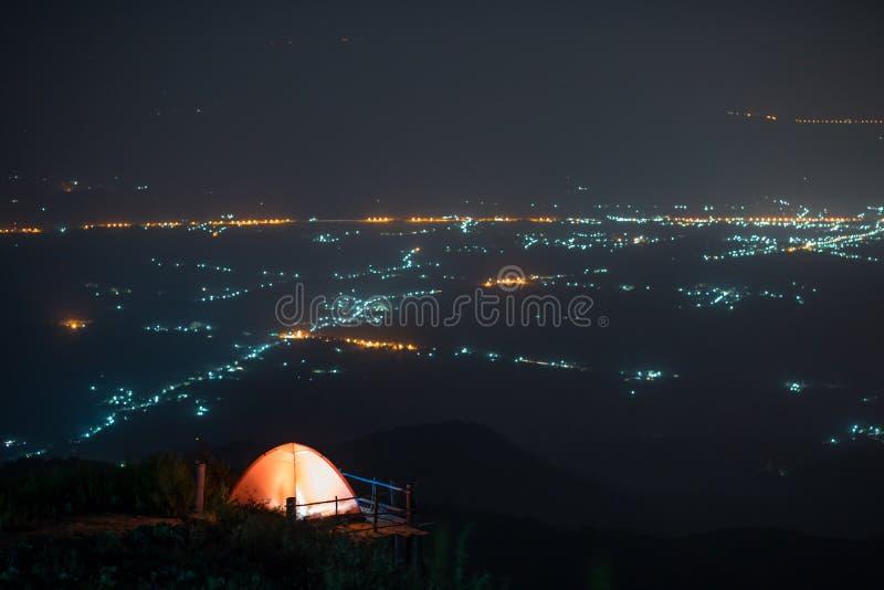 Tenda di campeggio sulla collina con la parte posteriore della luce della città immagine stock libera da diritti