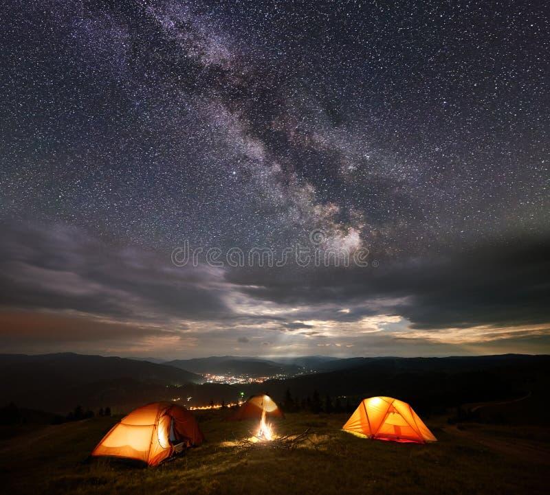 Tenda di campeggio sulla montagna alla notte sotto il cielo molto stellato contro della città luminosa fotografie stock