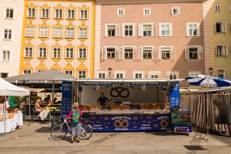 A tenda do mercado com pretzeis brezen no mercado no quadrado Universitatsplatz da universidade, Salzburg, Áustria fotografia de stock royalty free