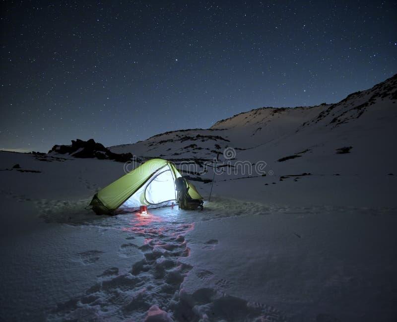 Tenda illuminata sulla neve congelata sotto il cielo stellato fotografia stock libera da diritti