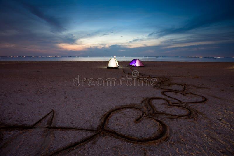 Tenda sulla spiaggia con il tramonto immagine stock