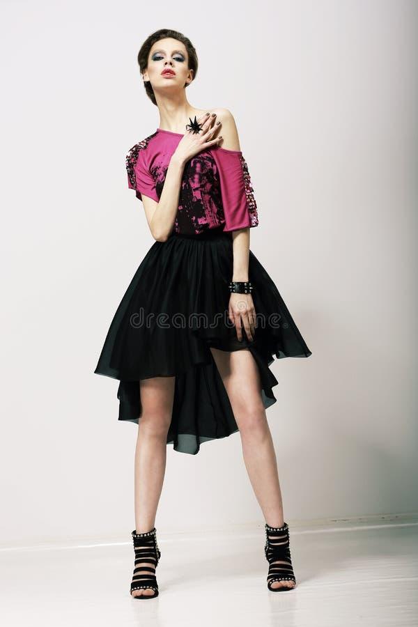 Tendance. Mannequin fascinant dans des vêtements modernes posant dans le studio photo stock
