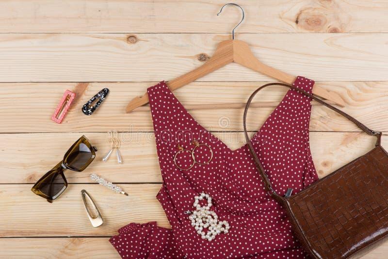 Tendances de mode - lunettes de soleil, sac, robe rouge dans des points de polka sur le cintre et bijoux : collier de perle, agra photos libres de droits