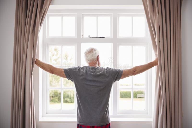 Tende della camera da letto di apertura dell'uomo senior e guardare dalla finestra fotografie stock libere da diritti