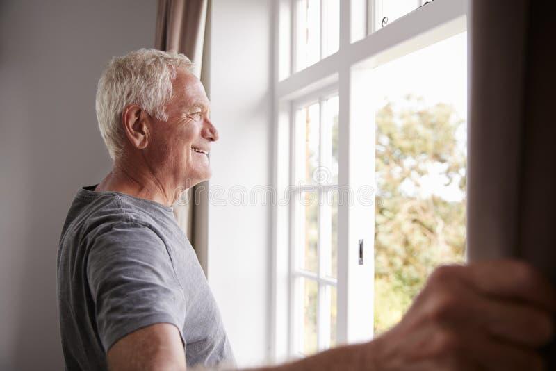 Tende della camera da letto di apertura dell'uomo senior e guardare dalla finestra fotografie stock
