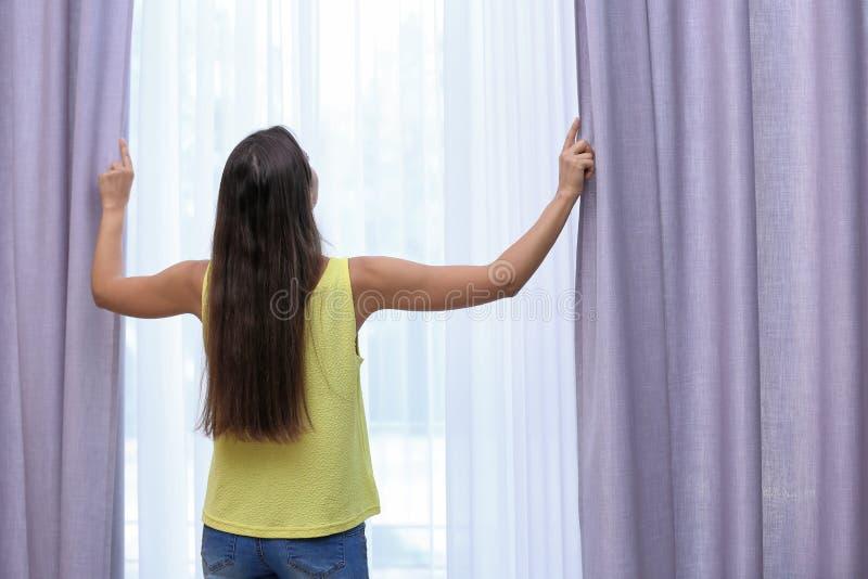 Tende di finestra di apertura della giovane donna immagini stock libere da diritti