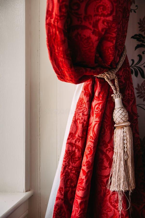 Tende rosse riunite del velluto con la nappa dell'oro in una vecchia en rustica fotografia stock libera da diritti