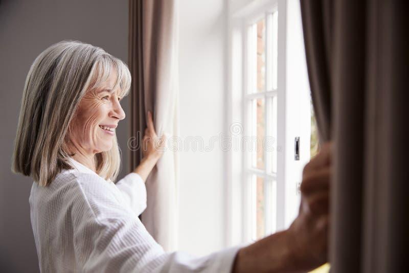 Tende senior della camera da letto di apertura della donna e guardare dalla finestra fotografia stock libera da diritti