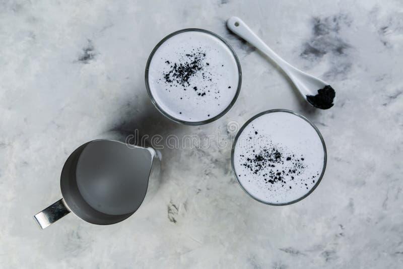 Tendencia de la comida - latte del carbón de leña en el fondo de mármol imagenes de archivo