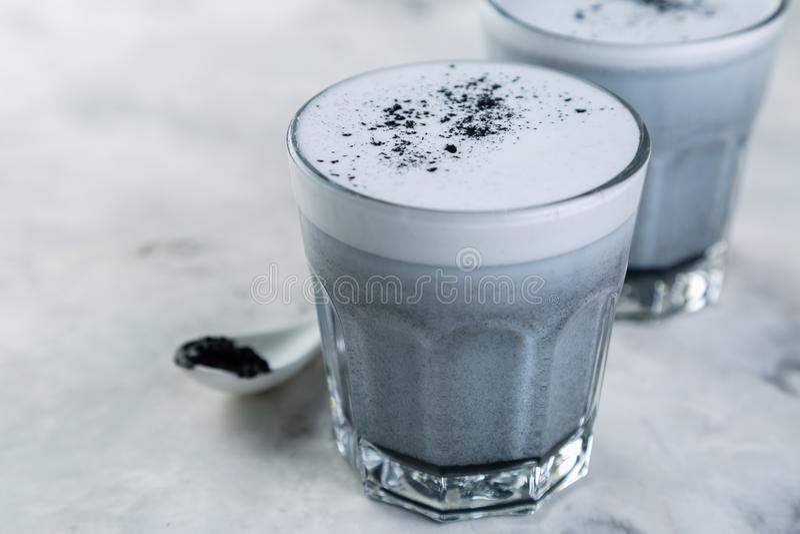 Tendencia de la comida - latte del carbón de leña en el fondo de mármol fotos de archivo libres de regalías