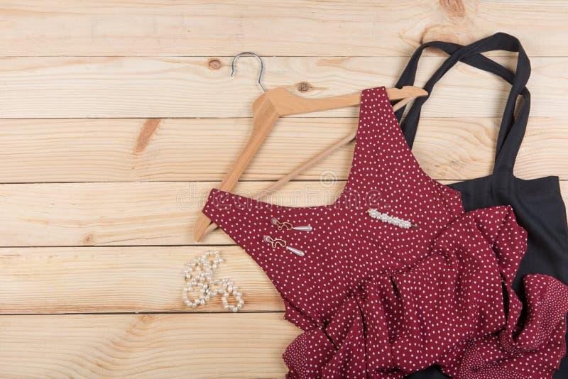 Tendencias de la moda - la bolsa de asas negra del eco, vestido rojo en lunares en la suspensi?n y joyer?a de la perla: collar, c fotos de archivo libres de regalías