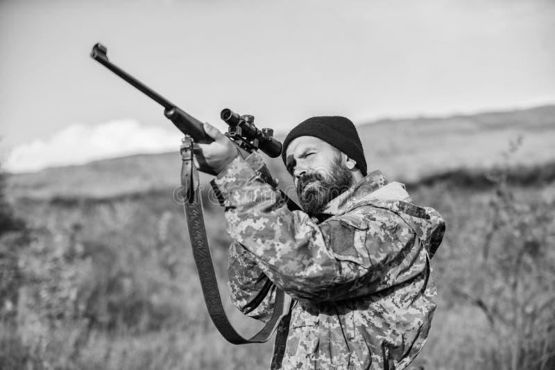 Tendenza delle abilit? Sul mio obiettivo Cacciatore barbuto spendere caccia di svago Cercare l'attrezzatura di ottica per i profe fotografia stock libera da diritti