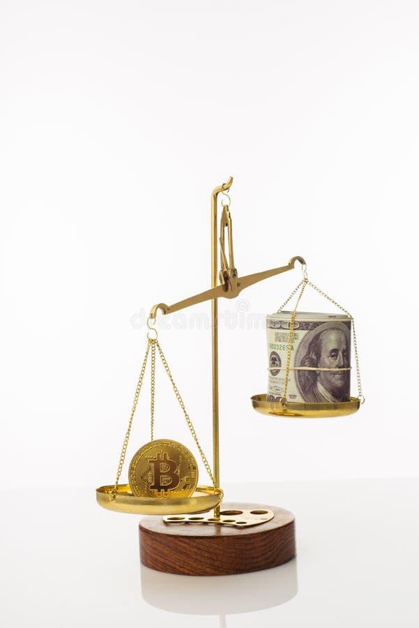Tendenza di aumento di valore di Bitcoin La moneta supera l'equilibrio in peso Su un'altra ciotola una pila di cento banconote in fotografia stock libera da diritti