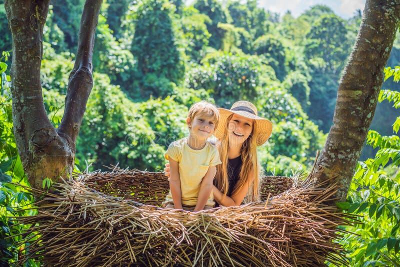 Tendenza di Bali, nidi della paglia dappertutto Famiglia felice che gode del loro viaggio intorno all'isola di Bali, Indonesia Fa immagine stock libera da diritti