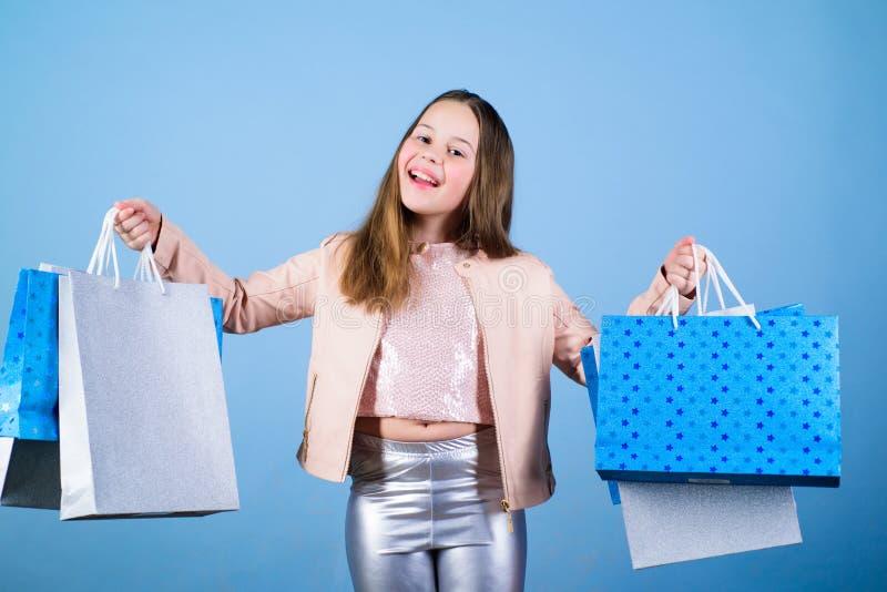 Tendenza di modo Negozio di modo Bambina con i pacchetti del mazzo Cliente della ragazza di modo Bambino felice in negozio con le fotografia stock