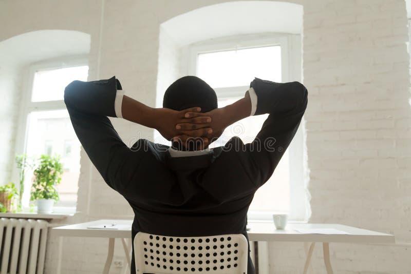 Tendenza di riposo dell'afroamericano rilassato indietro in sedia fotografia stock libera da diritti