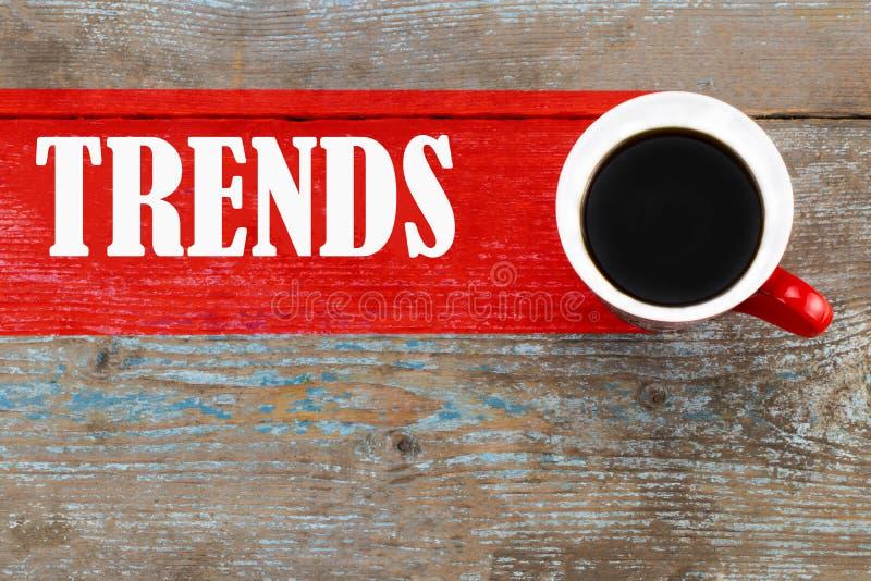Tendenze/tazza di caffè con l'iscrizione di tendenze sul backgro di legno immagini stock libere da diritti