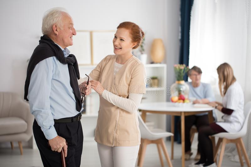 Tender attention of medical staff. Towards elderly men and woman, talking, explaining, comforting in luxury care facility common room royalty free stock image