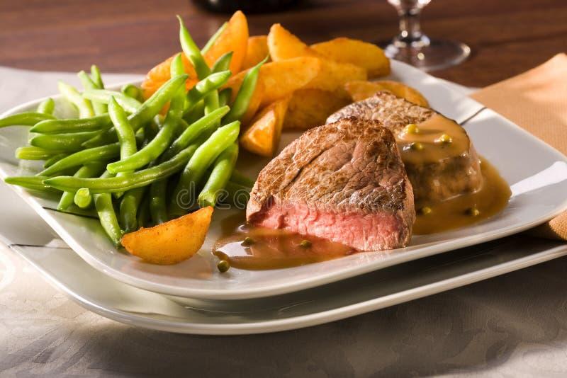 Tender beef fillet, green beans, wedges stock photos