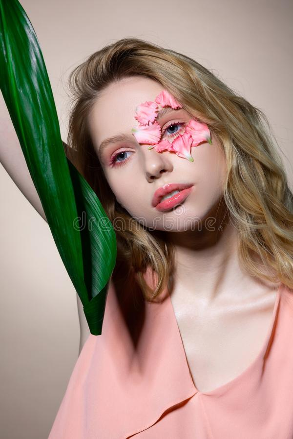 Tender blue-eyed model with pink lips and eyeshades holding leaf. With pink lips. Tender blue-eyed model with pink lips and eyeshades holding leaf while posing stock photos