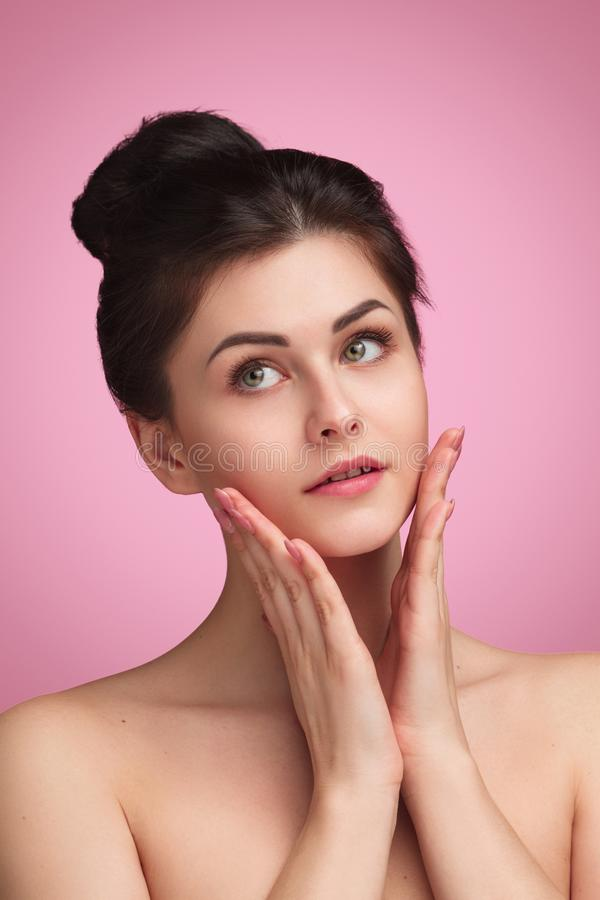 Tender brunette with clear skin. Charming young woman with soft tender and clean skin touching face and looking away on pink background stock images