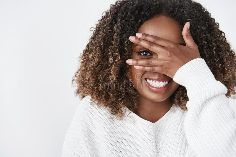 Tender and cute african american girlfriend hiding behind palm peeking through finger and smiling broadly as. Anticipating surprise fooling around and feeling stock photos