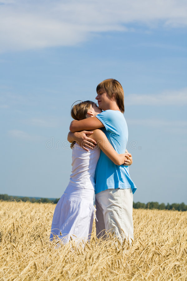 Tender embrace. Photo of loving couple in sweet embrace on the field of golden wheat stock photo