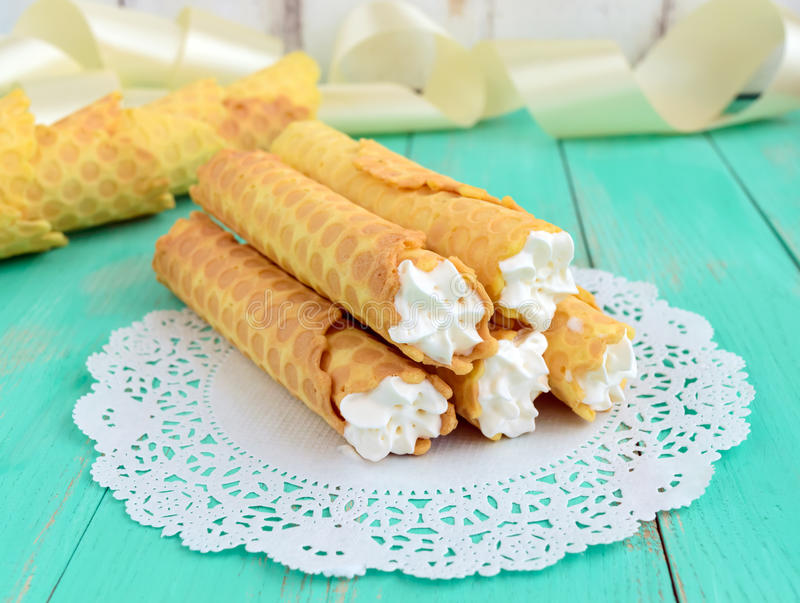 Tender honey wafers in the form of tubes, stuffed with air cream on white lace napkin. stock image