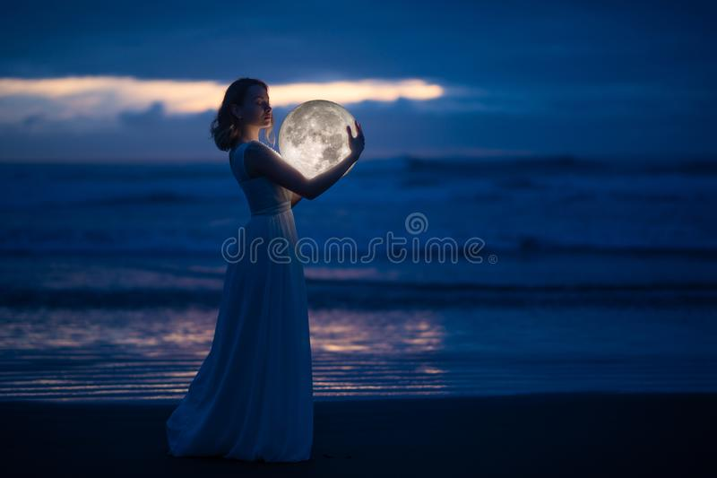 Tender image of a girl. Female magic. Beautiful attractive girl in full growth on a night beach with sand hugs the moon, art photo. On a dark background with stock photography