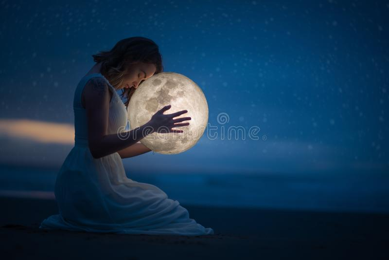 Tender image of a girl; female magic. Beautiful attractive girl on a night beach with sand and stars hugs the moon, art photo. On stock images