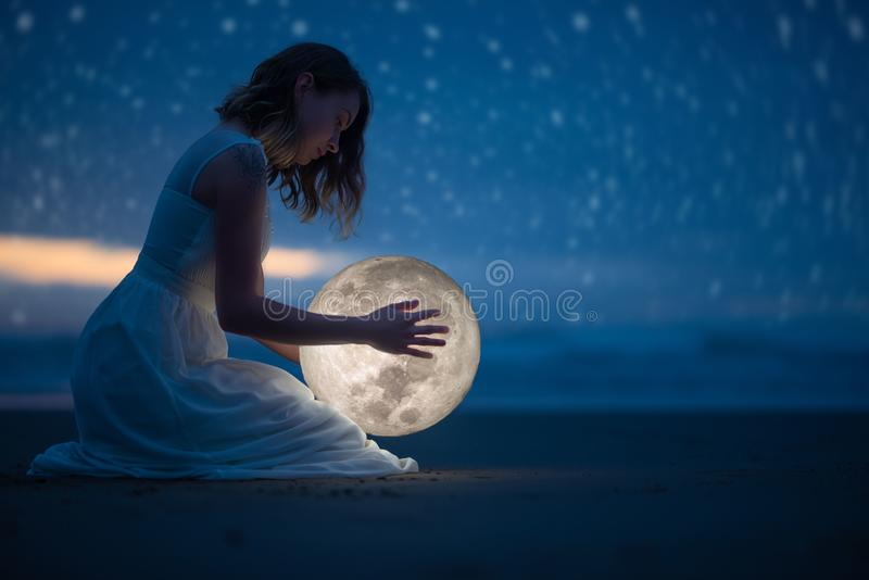 Tender image of a girl; female magic. Beautiful attractive girl on a night beach with sand and stars hugs the moon, art photo. On stock photography