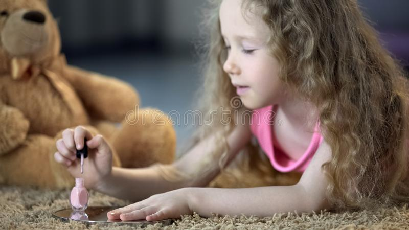 Tender little girl painting nails with polish, kid dreaming to grow up soon stock images