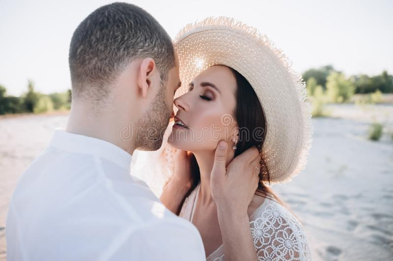 Tender man hugging and kissing beautiful woman. In hat stock images