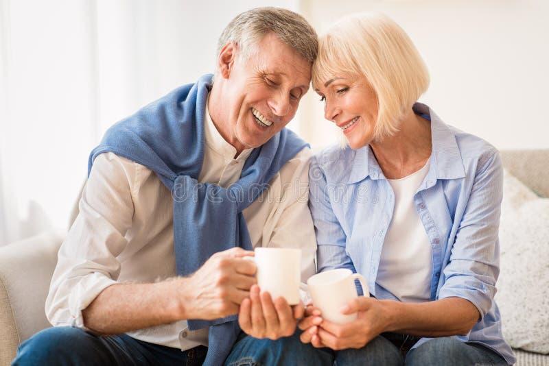 Tender mature couple drinking tea at autumn day stock photos