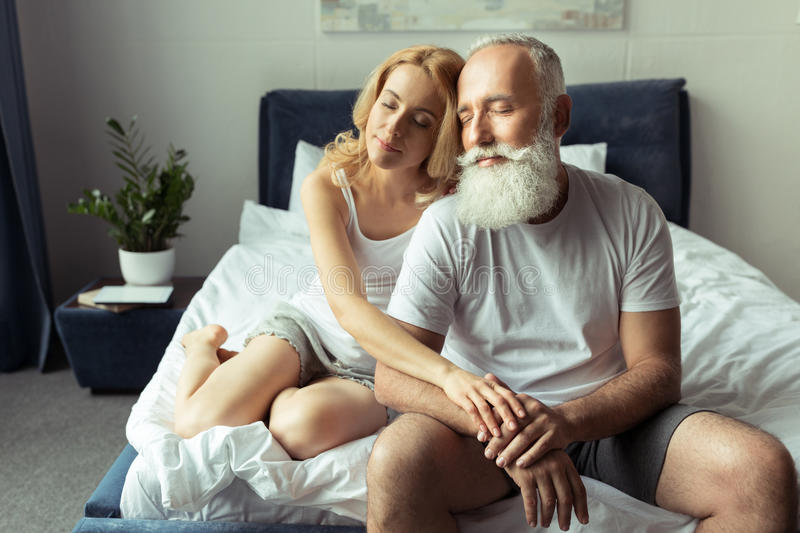 Tender mature couple embracing and relaxing on bed stock images