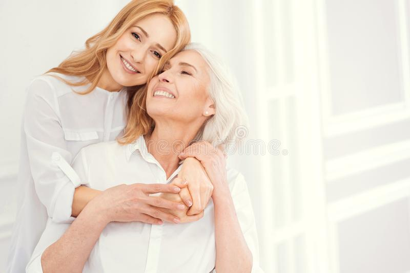 Tender mature woman embracing her senior mom with love. Love you to the moon and back. Full of love charming blonde lady smiling into the camera while standing royalty free stock photo