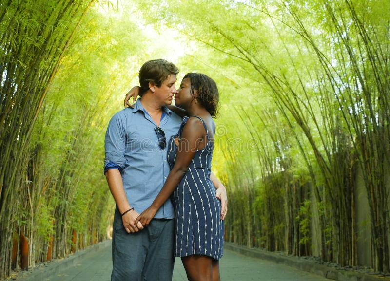 Tender mixed ethnicity couple cuddling outdoors with attractive black afro American woman and handsome Caucasian boyfriend or stock photography