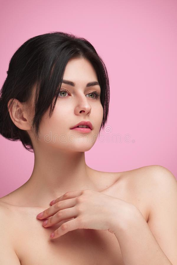 Tender model with soft skin on pink. Confident gentle girl with beautiful hairstyle standing on pink with hand on tender skin and looking away stock image