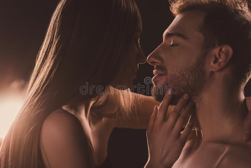 tender naked couple kissing and looking at each other, on brown stock photos
