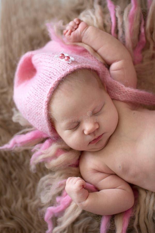 Tender newborn baby in pink cap sleeps stretching royalty free stock photos