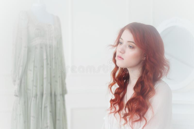 Tender portrait of a young dreamy redhead woman in nightdress. She is sitting in dress room and planning to wear beautiful vintage stock image