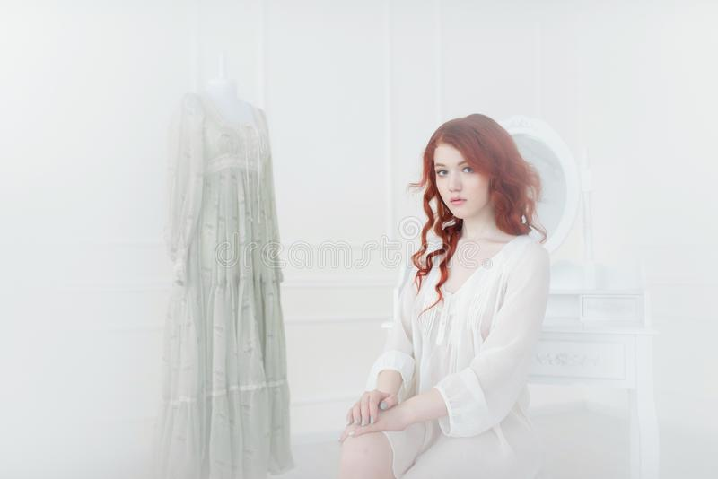Tender portrait of a young dreamy redhead woman in nightdress. She is sitting in dress room and planning to wear beautiful vintage stock photos