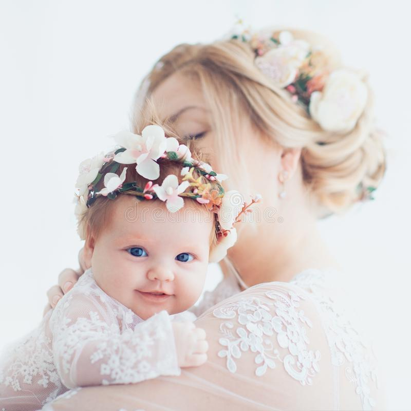 Tender portrait of young mother holding infant baby girl, daughter. family look outfit royalty free stock photography