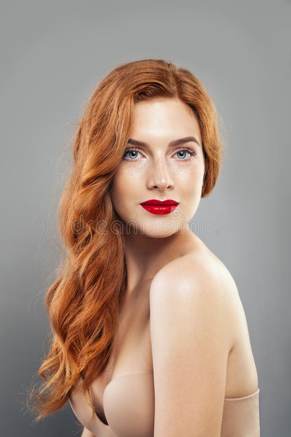 Tender redhead girl with healthy freckled skin. Caucasian woman model with ginger hair posing indoors royalty free stock image
