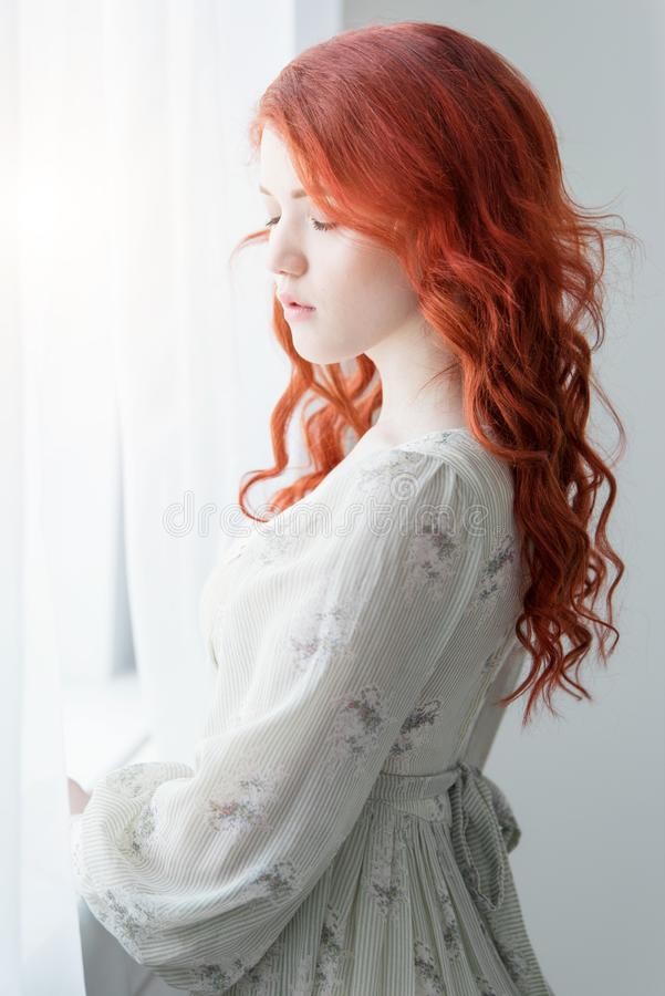 Tender retro portrait of a young beautiful dreamy redhead woman. stock photography