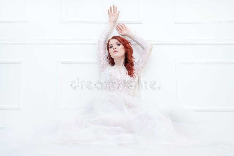 Tender retro portrait of a young beautiful dreamy redhead woman in beautiful white dress. royalty free stock photo