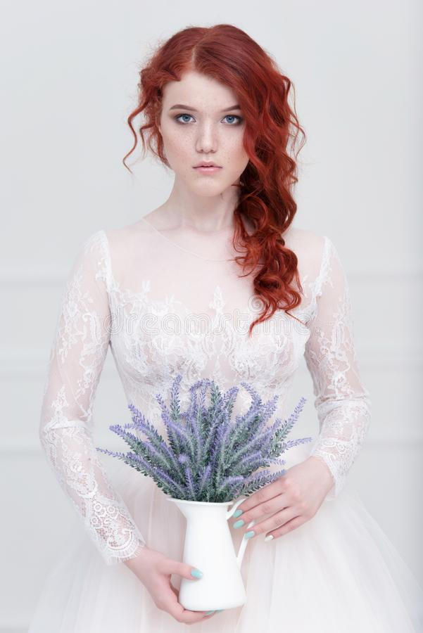 Tender retro portrait of a young beautiful dreamy redhead woman in beautiful white dress with bouquet of lavender. stock photo