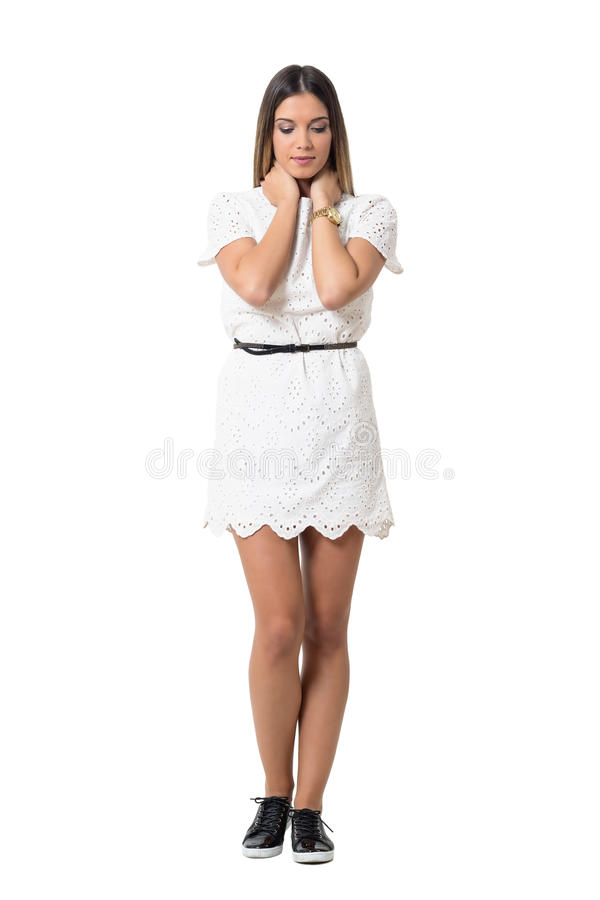 Tender sad beauty in white lace dress with hands on neck looking down stock photography